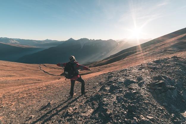 Männlicher wanderer, der bei sonnenuntergang am gebirgsgipfel sich entspannt und majestätisches panorama der italienischen alpen betrachtet