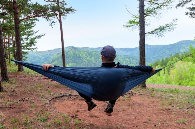 Männlicher wanderer, der in einer hängematte ruht, die natur im wald genießt