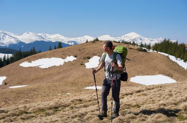 Männlicher wanderer mit rucksack in den bergen