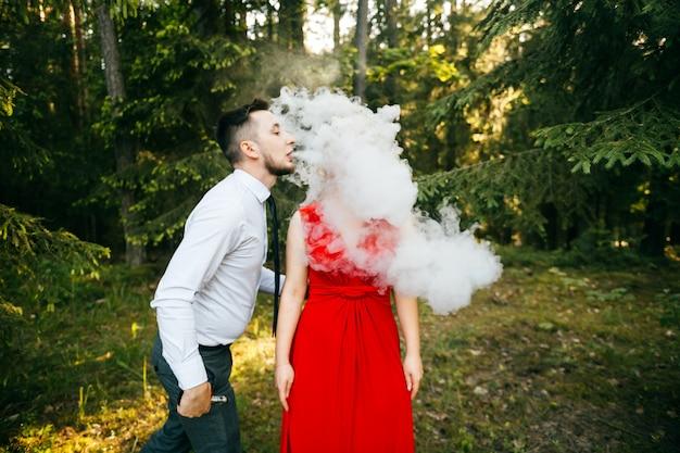 Männlicher wape-raucher, der dicke rauchwolke zum ohr seiner freundin im roten kleid mit lustigem emotionalem gesicht bläst.