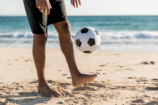 Männlicher werfender ball, der oben spiel am strand spielt