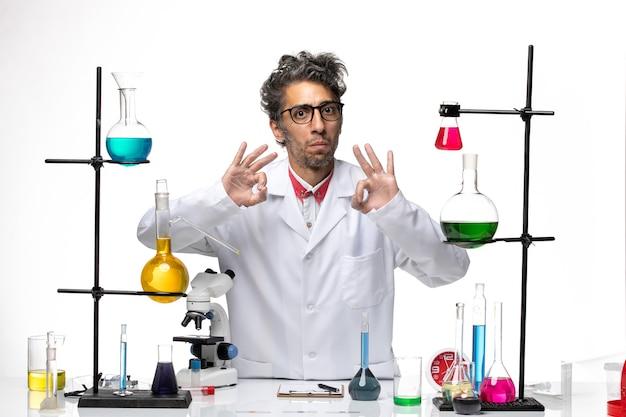 Männlicher wissenschaftler der vorderansicht, der mit lösungen aufwirft