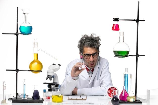 Männlicher wissenschaftler der vorderansicht im medizinischen anzug, der injektion auf covid-lab-virus der chemie des weißen hintergrunds hält