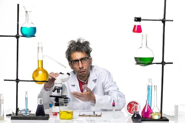 Männlicher wissenschaftler der vorderansicht im medizinischen anzug, der mit flaschen und lösungen arbeitet
