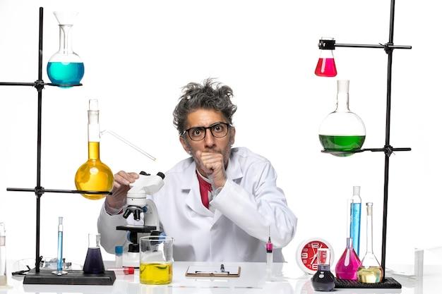 Männlicher wissenschaftler der vorderansicht im medizinischen anzug, der mit mikroskop arbeitet
