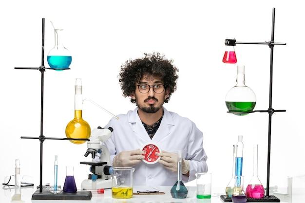 Männlicher wissenschaftler der vorderansicht im medizinischen anzug, der rote uhren auf dem hellen weißen raum hält