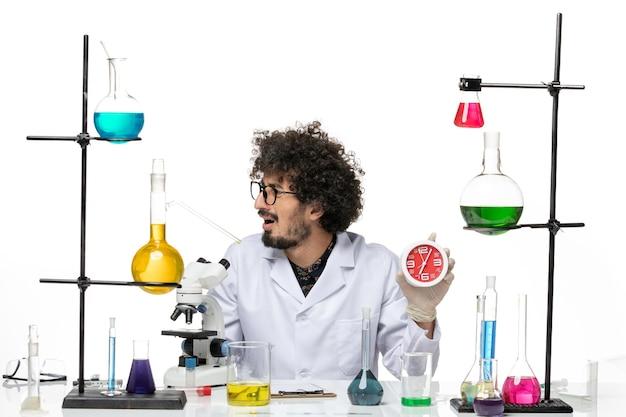 Männlicher wissenschaftler der vorderansicht im medizinischen anzug, der rote uhren auf weißem raum hält