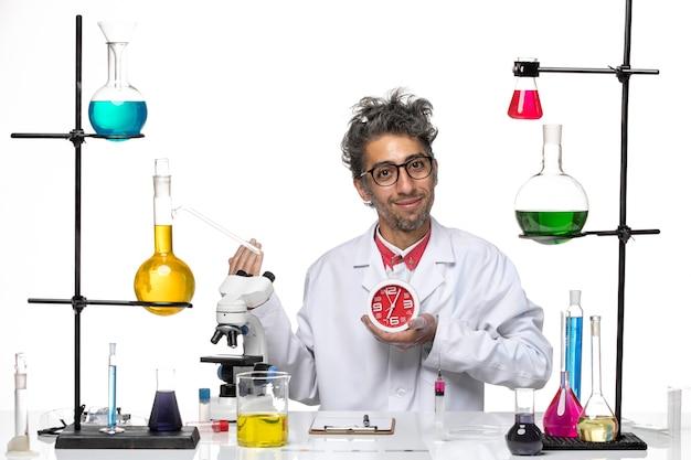 Männlicher wissenschaftler der vorderansicht im medizinischen anzug, der runde uhren auf gesundheit des weißen hintergrundchemie-covid-lab-virus hält