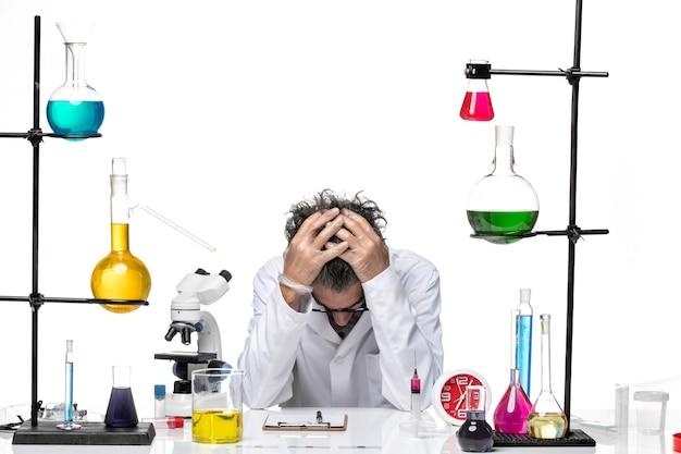 Männlicher wissenschaftler der vorderansicht im medizinischen anzug, der sich auf der chemie des weißen hintergrundviruslabors müde fühlt