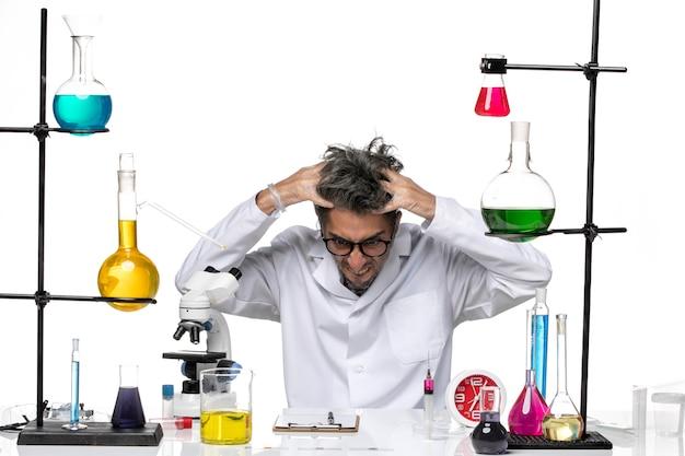 Männlicher wissenschaftler der vorderansicht im medizinischen anzug, der sich auf der chemie des weißen hintergrundviruslabors wütend fühlt