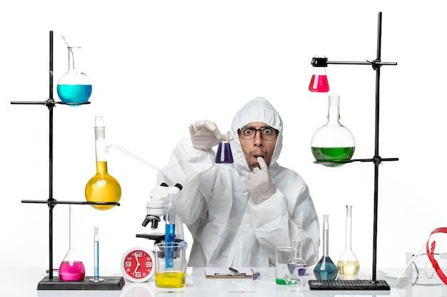 Männlicher wissenschaftler der vorderansicht im speziellen schutzanzug, der flasche mit lösung hält