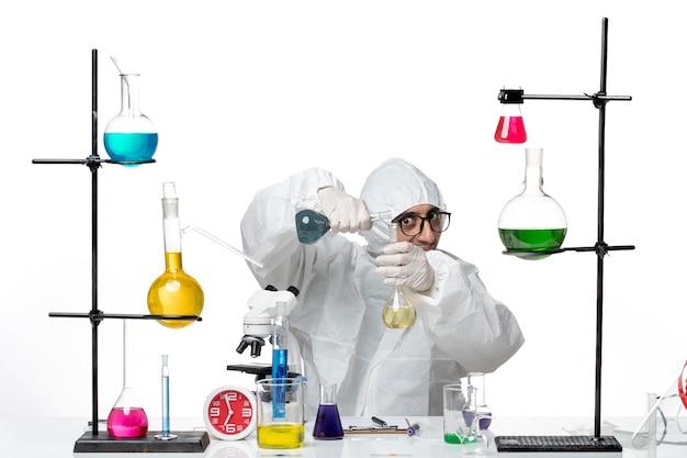 Männlicher wissenschaftler der vorderansicht im speziellen schutzanzug, der flaschen mit lösungen hält