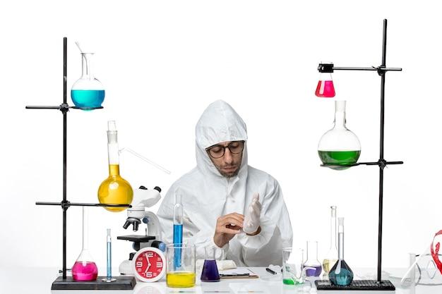 Männlicher wissenschaftler der vorderansicht im speziellen schutzanzug, der mit lösungen um tisch sitzt