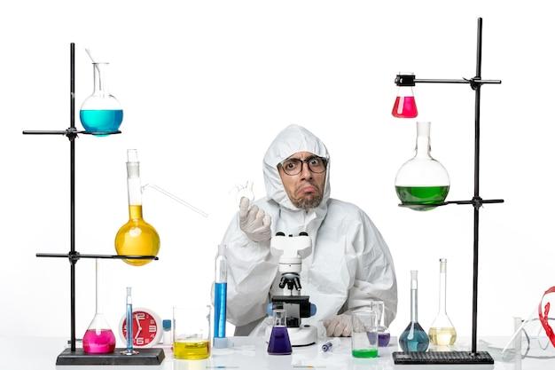 Männlicher wissenschaftler der vorderansicht im speziellen schutzanzug, der mit verschiedenen lösungen sitzt