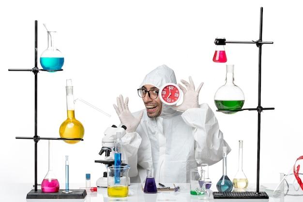 Männlicher wissenschaftler der vorderansicht im speziellen schutzanzug, der rote uhren hält