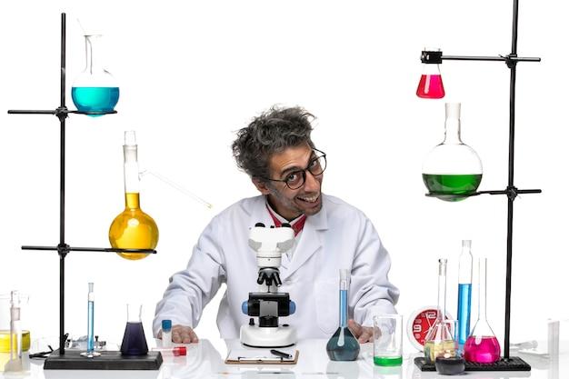 Männlicher wissenschaftler der vorderansicht im weißen medizinischen anzug breit lächelnd