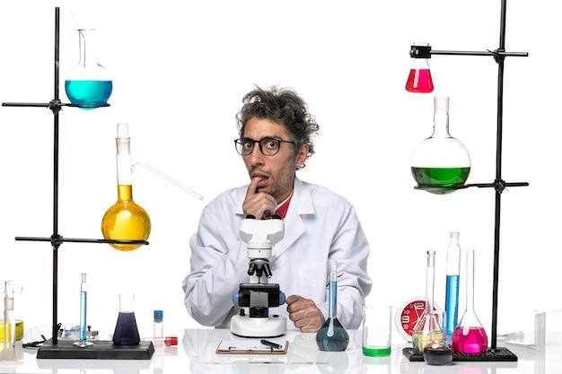 Männlicher wissenschaftler der vorderansicht im weißen medizinischen anzug, der lustiges gesicht macht