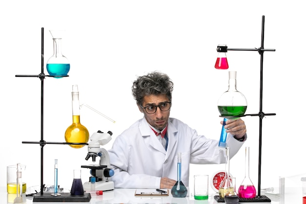 Männlicher wissenschaftler der vorderansicht im weißen medizinischen anzug, der mit lösungen arbeitet