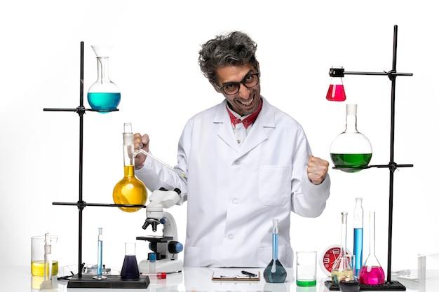 Männlicher wissenschaftler der vorderansicht im weißen medizinischen anzug, der sich freut