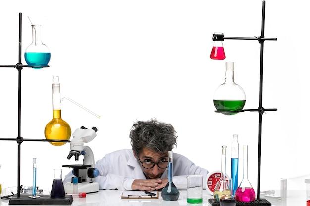 Männlicher wissenschaftler der vorderansicht im weißen medizinischen anzug, der vor dem tisch mit lösungen sitzt