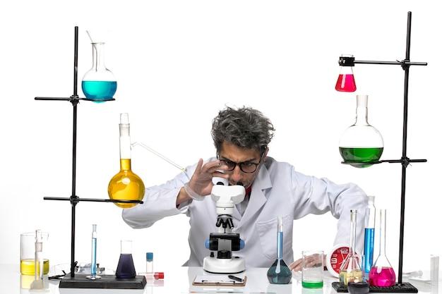 Männlicher wissenschaftler der vorderansicht im weißen medizinischen anzug unter verwendung des mikroskops