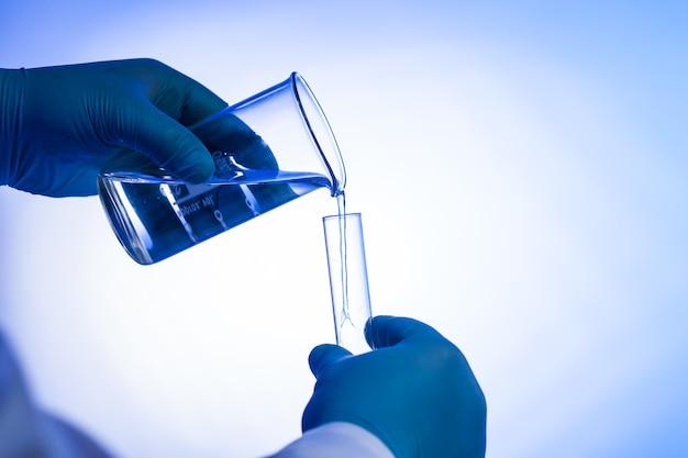 Männlicher wissenschaftler gießt flüssigkeit aus becherglas in reagenzglas