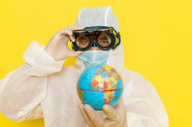 Männlicher wissenschaftlicher arbeiter der vorderansicht im speziellen anzug, der kleine runde kugel auf gelber oberfläche hält