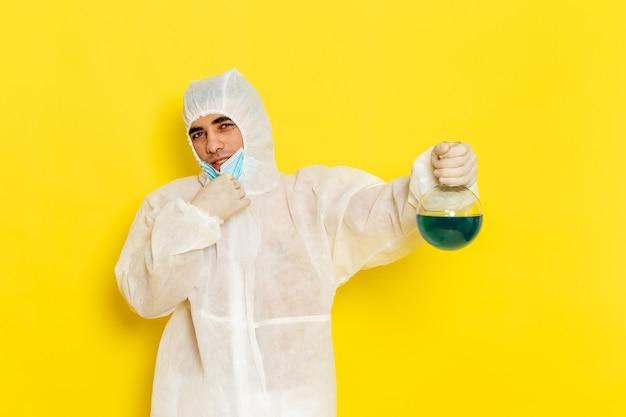 Männlicher wissenschaftlicher arbeiter der vorderansicht im speziellen schutzanzug, der flasche mit blauer lösung auf gelber oberfläche hält