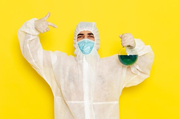 Männlicher wissenschaftlicher arbeiter der vorderansicht im speziellen schutzanzug, der flasche mit blauer lösung auf hellgelber oberfläche hält