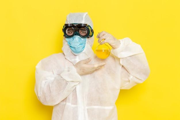 Männlicher wissenschaftlicher arbeiter der vorderansicht im speziellen schutzanzug, der flasche mit gelber lösung auf gelber oberfläche hält