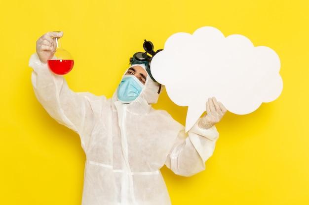 Männlicher wissenschaftlicher arbeiter der vorderansicht im speziellen schutzanzug, der flasche mit roter lösung und großem weißem schild auf hellgelbem schreibtisch hält