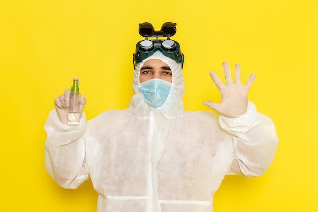 Männlicher wissenschaftlicher arbeiter der vorderansicht im speziellen schutzanzug, der spray auf hellgelber oberfläche hält