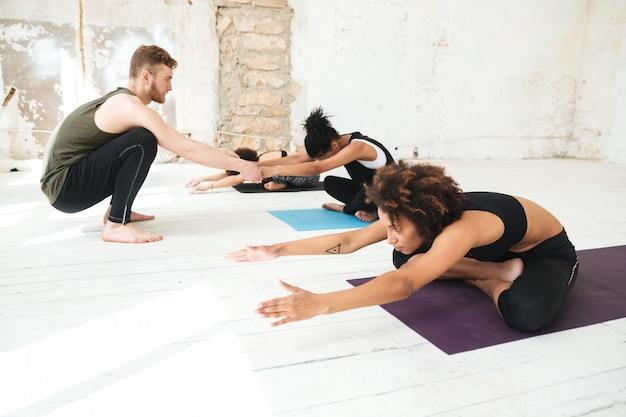 Männlicher yogalehrer, der einer frau hilft, yoga-strecken zu machen