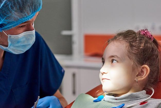 Männlicher zahnarzt, der die zähne des kleinen mädchens überprüft