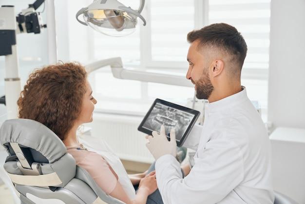 Männlicher zahnarzt, der in der modernen zahnmedizinischen klinik arbeitet