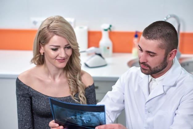 Männlicher zahnarzt, der röntgenstrahl patienten erklärt