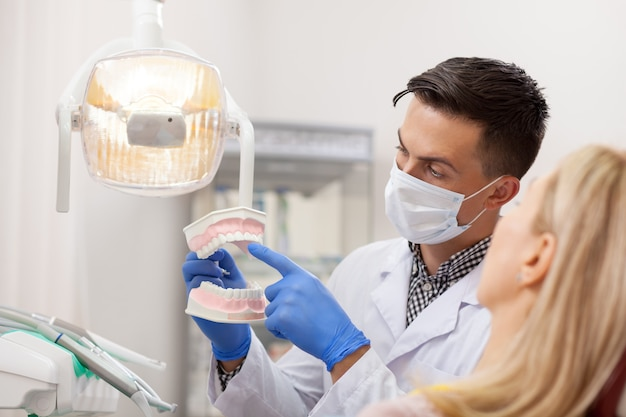 Männlicher zahnarzt, der seinen weiblichen patienten über zahnsorgfalt erklärt