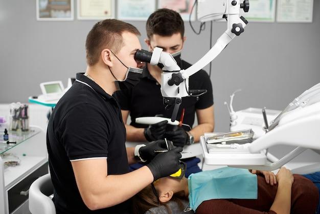 Männlicher zahnarzt führt zahnuntersuchung durch