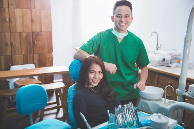 Männlicher zahnarzt in der klinik mit weiblichem patienten
