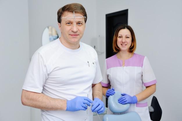 Männlicher zahnarzt mit behilflichen medizinischen instrumenten und mädchen in der klinik