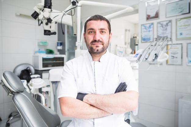 Männlicher zahnarzt mit den gefalteten händen in der klinik