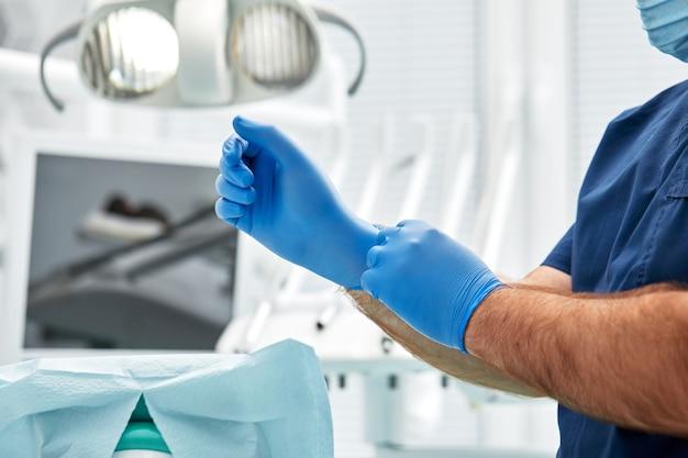 Männlicher zahnarzt zieht handschuhe gegen einen raum der zahnärztlichen ausrüstung in einer zahnarztpraxis an. glückliches patienten- und zahnarztkonzept.