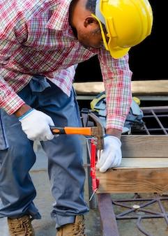 Männlicher zimmermann, der einen hammer benutzt, um einen nagel in holzbrett zu schlagen. werkzeuge und geräte für das holzbearbeitungskonzept.