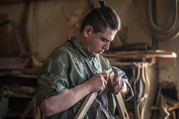 Männlicher zimmermann, der mit einem holzprodukt arbeitet, handwerkzeuge, nahaufnahme