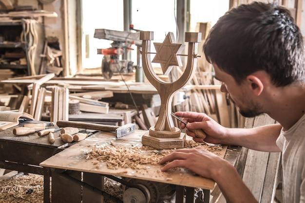 Männlicher zimmermann, der mit einem holzprodukt arbeitet, handwerkzeuge