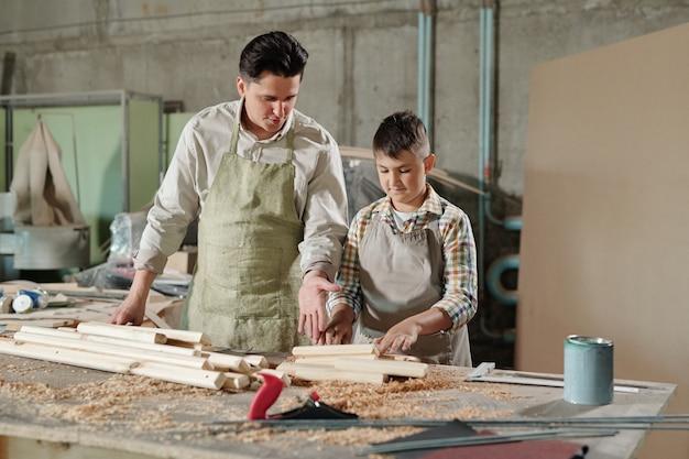 Männlicher zimmermann in der schürze, die auf planken zeigt, während er jugendlichen sohn erklärt, wie man mit holz in der möbelwerkstatt arbeitet