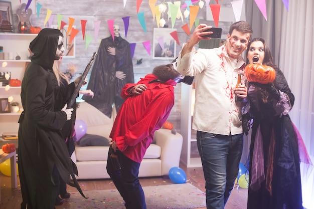 Männlicher zombie, der ein selfie mit einer hexe hält, die einen kürbis bei halloween-feier hält.