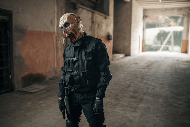 Männlicher zombie, der in verlassener fabrik geht