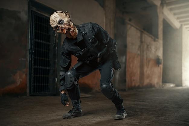 Männlicher zombie, der in verlassener fabrik, unheimlicher ort geht. horror in der stadt, gruselige krabbeltiere, weltuntergangsapokalypse, blutige böse monster