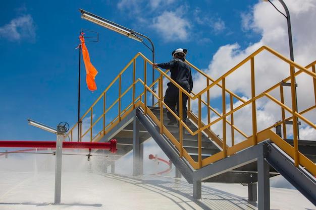 Männliches arbeiter inspektionsrohr wasser sprüht feuertanks gas propan dachtank mit feuerlöscher und kühlsystem.